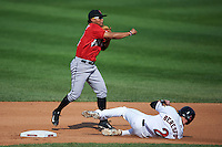 Indianapolis Indians shortstop Gustavo Nunez (12) throws to first as James Beresford (2) slides in during a game against the Rochester Red Wings on June 10, 2015 at Frontier Field in Rochester, New York.  Indianapolis defeated Rochester 5-3.  (Mike Janes/Four Seam Images)