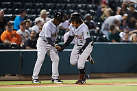 Jahmai Jones (2) of the Norfolk Tides slaps hands with third base coach Ramon Sambo (16) after hitting a home run against the Charlotte Knights at Truist Field on August 19, 2021 in Charlotte, North Carolina. (Brian Westerholt/Four Seam Images)