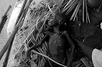 Kalma IDP camp, South Darfur, July 29 2004.The body of Abacar Abdallah, 25 months old, is being washed before burial after he died from severe malnutrition, weighing at only 5.2kg, despite desperate last minute efforts by MSF medical staff to save him.