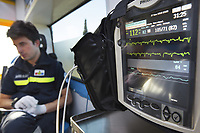 Switzerland. Canton Ticino. Lugano. A paramedic seated in an ambulance during a medical emergency intervention. The paramedic wears a blue uniforms and works for theCroce Verde Lugano. The man is a professional certified nurse. He checks the patient's state with a Philips monitor controlling a set of vital functions, such as  electrocardiogram, blood pressure's measurement, respiratory rate and pulse oximetry (oxygen saturation). TheCroce Verde Lugano is a private organization which ensure health safety by addressing different emergencies services and rescue services. 27.01.2018 © 2018 Didier Ruef