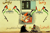 TITLE - DISTANT RELATIONS, PALESTINIAN GRAFFITI COVERS WALLS BEHIND TWO ARAB MEN,. JABALYA CAMP.