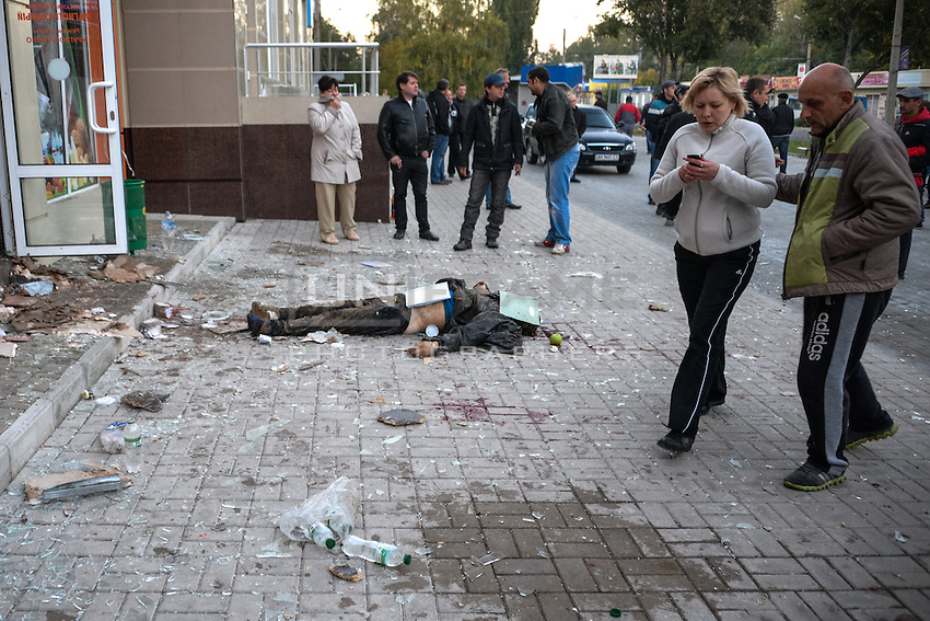 People watch a civilian killed by shrapnel from shelling on the street of Donetsk, Eastern Ukraine