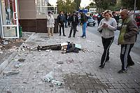 People watch a civilian killed by shrapnel from shelling on the street of Donetsk, Eastern Ukraine