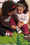 Preschool New York City ages 4-5 one girl tying the shoelaces of a friend