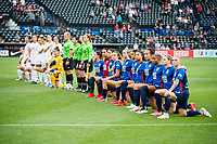 TACOMA, WA - JULY 31: OL Reign kneel together during the national anthem during a game between Racing Louisville FC and OL Reign at Cheney Stadium on July 31, 2021 in Tacoma, Washington.