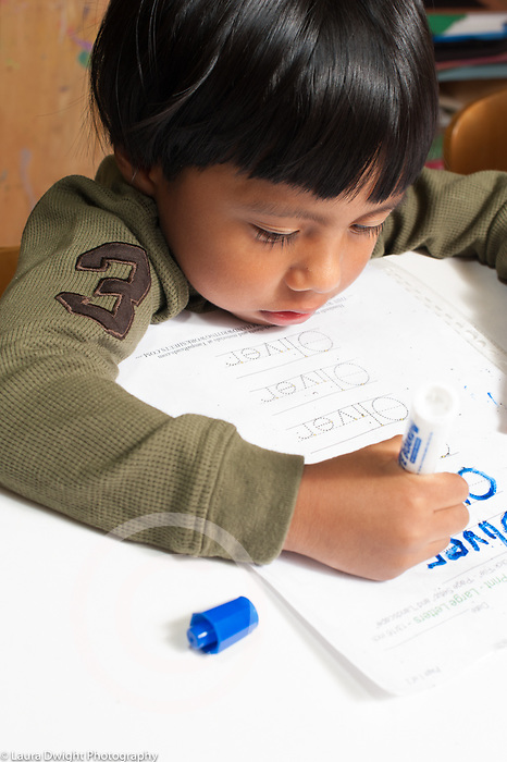 Education preschool 3-4 year olds boy writing or tracing letters of his name