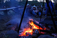Guests talk and laugh around the campfire at the Wild Horse Sanctuary. Overnight rides through the ranch end to view mustangs at this rustic site with cabins.<br />