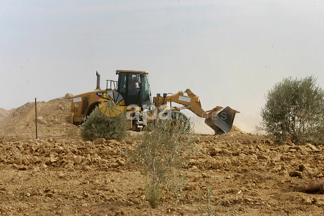 A Palestinian uses a digger in front of International Committee of the Red Cross (ICRC) workers as the comittee assists Palestinian farmers to repair their fields that were devastated during the Israeli army summer's military offensive on the Gaza Strip on October 22, 2014, in Khan Yunis' Khuzaa neighbourhood in the southern Gaza Strip near the Israeli border. Photo by Abed Rahim Khatib