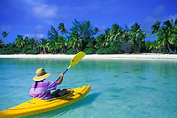 Kayaker steers toward motu in the blue lagoon off Aitutaki, Cook Islands