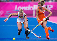 29 JUL 2012 - LONDON, GBR - Ellen Hoog (NED) of Netherlands (right) tries to avoid a tackle from Anne-Sophie van Regemortel (BEL) of Belgium (left) during their women's London 2012 Olympic Games Preliminary round hockey match at the Riverbank Arena in the Olympic Park in Stratford, London, Great Britain .(PHOTO (C) 2012 NIGEL FARROW)