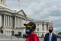 """Michael Wheeler, of Kansas City, MO, (left) wears his """"Super Jesus"""" outfit and face mask while a US Capitol Security detail stands at right as House Minority Leader Rep. Kevin McCarthy (R-Calif.) holds a media availability with House Minority Whip Rep. Steve Scalise (R-LA), House GOP Conference Chairwoman Liz Cheney (R-WY) and others, to announce that Republican leaders have filed a lawsuit against House Speaker Nancy Pelosi and congressional officials in an effort to block the House of Representatives from using a proxy voting system to allow for remote voting during the coronavirus pandemic, outside of the U.S. Capitol in Washington, DC., Wednesday, May 27, 2020. Credit: Rod Lamkey / CNP/AdMedia"""
