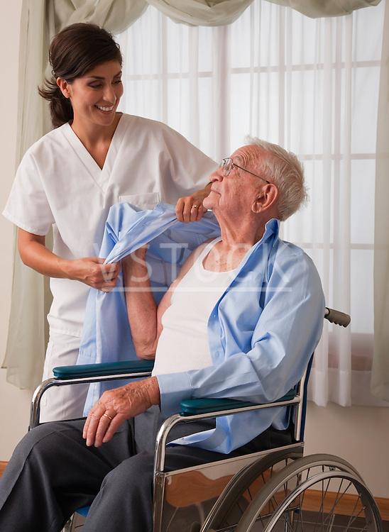 USA, Illinois, Metamora, Female nurse assisting senior man in dressing himself