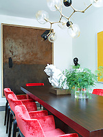 In the dining room, bold red armchairs by Caste and upholstered in a Holly Hunt velvet, surround a circa 1960 dining table by Milo Baughman. A display of ferns in a glass vase and a sculpture by Rachel Feinstein stand on the table. The chandelier above is by Lindsey Adelman and on one wall a painting by Alex Katz.