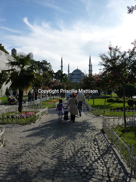 Istanbul, Turkey - September 24, 2009:   People walk through the garden toward the Blue Mosque.
