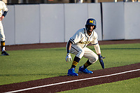 Michigan Wolverines outfielder Christian Bullock (5) takes a lead off of third base against the Michigan State Spartans on March 21, 2021 in NCAA baseball action at Ray Fisher Stadium in Ann Arbor, Michigan. Michigan scored 8 runs in the bottom of the ninth inning to defeat the Spartans 8-7. (Andrew Woolley/Four Seam Images)