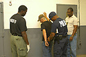 New Orleans sheriff deputies take off the handcuffs of a suspect that will be held in the temporary jail that just opened in New Orleans, October 18, 2005.<br /> (AP Photo/Cheryl Gerber)