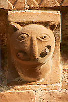 Norman Romanesque exterior corbel no 29  -  sculpture of.a creature with a rounded head, pointed ears and a beaked nose. In its huge mouth it is biting on a rod . The Norman Romanesque Church of St Mary and St David, Kilpeck Herefordshire, England. Built around 1140