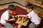 Preschool 4 year olds idendtical twin boys playing with blocks using opposite hands