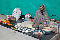 India, Rishikesh.  Woman Selling Flower Offerings and Snacks.