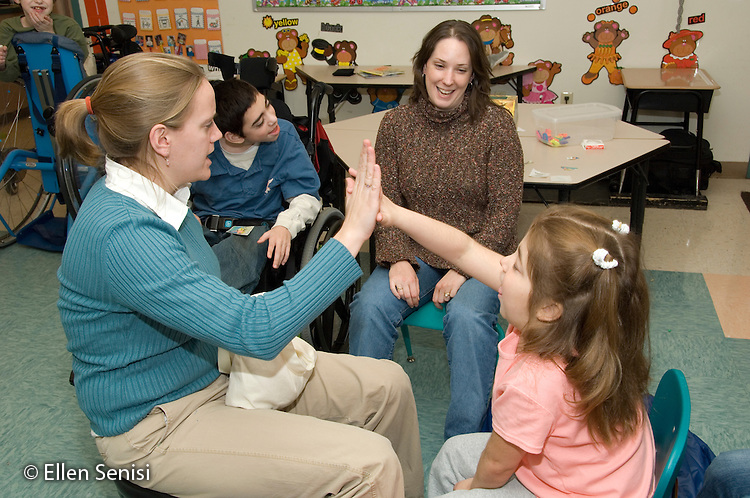 """MR / Albany, NY.Langan School at Center for Disability Services .Ungraded private school which serves individuals with multiple disabilities.Child gets a """"high five"""" from her teacher after participating in counting lesson. Girl: 11, cerebral palsy, non verbal with expressive and receptive language delays.MR: Ris4,Gor3.© Ellen B. Senisi"""
