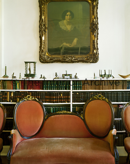 The conversation piece. A classical lady looks down over a love seat in the library of a Victorian-era New Orleans home