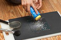 Fingerabdruck, Fingerabdrücke nehmen, 2. Schritt:  auf die Glasscheibe wird Puder gestreut, sammeln, sichten, vergleichen