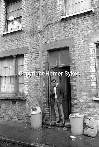 Tower Hamlets, Whitechapel East London 1975 UK. Peabody Estate, Princess Street multiracial block of flats 1970s Britain.  Bengali man in doorway.