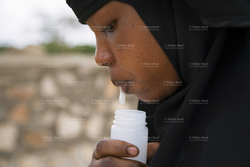 Somaliland. Waqohi Galbed province. Hargeisa. Tubeculosis (TB) hospital. A black muslim woman, wearing a veil on her hair, spits sputum in a plastic sputum cup. She is a suspected tuberculosis (TB) case. The Global Fund through the ngo ( non-governmental organization ) World Vision supports the programm with a Tuberculosis grant (financial aid). Somaliland is an unrecognized de facto sovereign state located in the Horn of Africa. Hargeisa is the capital of Somaliland. © 2006 Didier Ruef
