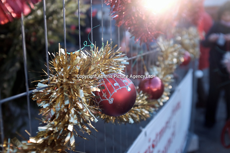 """Pictured: Local people help decorate the Christmas tree in Neath, south Wales, UK. Saturday 03 December 2016<br /> Re: Residents are making their own decorations for Neath's Christmas tree this year after complaints about the town's festive decorations.<br /> Neath resident Darren Bromham-Nichols is calling on others to create their own decorations for the tree near the town centre, which has been described as """"bare with lots of dead wood."""", although the town council has said it has received no complaints.<br /> He hopes this will make Neath Town Council, who have funded the Christmas decorations for the town, take notice and help to decorate the tree."""