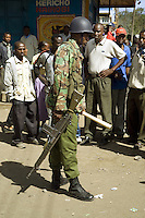 Kenya. Rift Valley province. Nakuru. 25.01.2008. A black Kikuyu policeman with military outfitts stands close to a group of men. He wears a helmet on the head. He also carries a wood stick in his left hand and a M16 machine gun in his right hand. M16 (more formally United States Rifle, Caliber 5.56 mm, M16) is the U.S. military designation for a family of rifles derived from the ArmaLite AR-15 and further developed by Colt starting in the mid-20th century.. The policeman is on duty because of the Inter-ethnic strife. Ethnic cleansing and purification. The Kikuyus are Kenya's most populous ethnic group. © 2008 Didier Ruef
