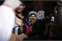 Pictured: A young woman covers her face as she is handed out food Monday 07 March 2016<br /> Re: Migrants have been gathering at the port of Piraeus, near Athens, Greece.