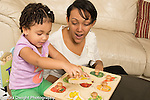 Toddler girl, age 2, at home, playing with fruit shapes peg puzzle, encouraged by mother