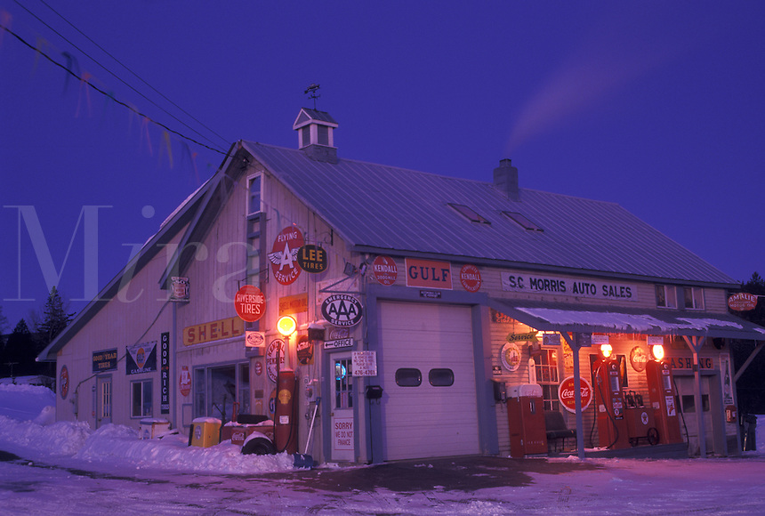 gas station, Vermont, VT, Gas station and garage with antique gas pumps lit up at night in the village of Orange in the snow in winter.