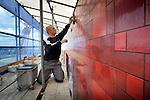 AMERSFOORT - In Amersfoort werken Duitse tegelzetters aan de vuurrode gevel van de nieuwe door van Vannel Bouwbedrijf uit Eindhoven gebouwde Hogeschool Utrecht(HU). In opdracht van Burgfonds in Zaltbommel ontwierp DP6 Architectuurstudio uit Delft het lange 18.000 m2 grote gebouw dat de blikvanger zal worden voor het vernieuwde Eemplein. Omdat alle tegels volgens een bepaald patroon geplaatst moeten worden, is momenteel een ploeg van tegelzetters op de steigers bezig het gebouw kleur te geven. COPYRIGHT TON BORSBOOM