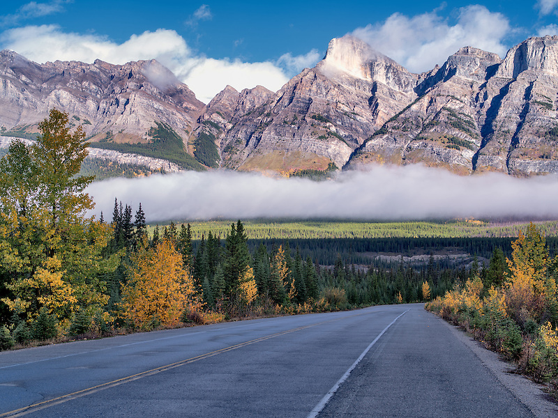 Road, fog and low clouds with autumn colors. Banff National Park. Alberta, Canada