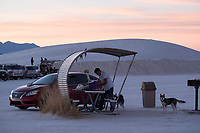 A man grills steaks with his dogs as the sun sets at White Sands National Monument near Alamogordo, New Mexico, USA, on Sat., Dec. 30, 2017.
