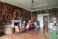 A red reception room, its walls hung with a multitude of 17th century portrait paintings