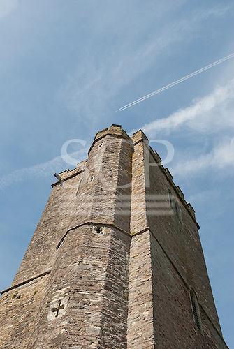 East Ogwell, Devon, England. Old tower of St Bartholomew's church and plane flying by.