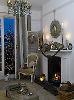 The living room at night decorated for Christmas with candles and traditional decorations and the tree lit outside the French windows