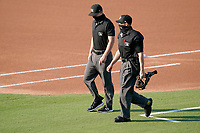 Umpires Adam Pierce, left, and Jose Lozada arrive to work a game between the Hickory Crawdads and the Greenville Drive on Friday, June 18, 2021, at Fluor Field at the West End in Greenville, South Carolina. (Tom Priddy/Four Seam Images)