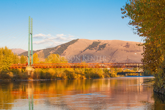 View of Missoula looking upriver on the Clark Fork. The California Street footbridge across the river. Mount Jumbo in the background.