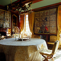 In the informal dining room the round table is covered by a pretty quilted tablecloth and a framed collection of dried flowers is displayed on the walls