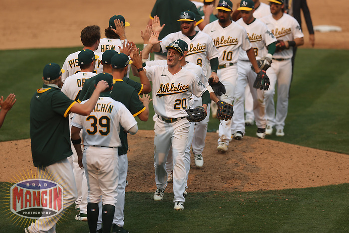 OAKLAND, CA - OCTOBER 1:  Mark Canha #20 of the Oakland Athletics celebrates with his teammates after the last out against the Chicago Sox to win Wild Card Round Game Three and the payoff series at the Oakland Coliseum on Thursday, October 1, 2020 in Oakland, California. (Photo by Brad Mangin)