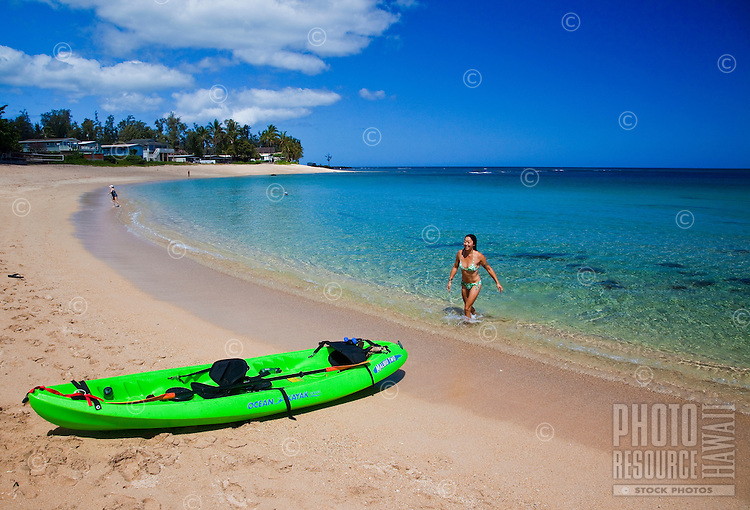 A young Asian woman enjoying the beach after paddling her kayak down the coast of Mokuleia