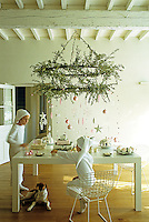Two boys sit at a table laid for afternoon tea beneath a candelabra covered in olive branches and pink and white Christmas decorations