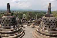 Borobudur, Java, Indonesia.  Stupas near the top of the Borobudur temple.  The diamond-shaped holes symbolize the passions that still linger as men rise toward Nirvana.