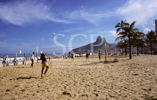 Rio de Janeiro, Brazil. People playing volleyball on Ipanema beach with the Dois Irmaos and palm trees.