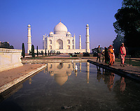 Early morning visitors in red saris pass a tiled waterway reflecting the Taj Mahal under a glorious blue sky, Agra, Indi