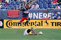 FOXBOROUGH, MA - MAY 16: Teal Bunbury #10 of New England Revolution leaps over a slide tackle by Waylon Francis #14 Columbus SC during a game between Columbus SC and New England Revolution at Gillette Stadium on May 16, 2021 in Foxborough, Massachusetts.