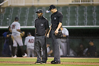 Umpires Darrell Roberts (left) and Mark Bass between innings of the South Atlantic League game between the Hickory Crawdads and the Kannapolis Intimidators at Kannapolis Intimidators Stadium on April 22, 2017 in Kannapolis, North Carolina.  The Intimidators defeated the Crawdads 10-9 in 12 innings.  (Brian Westerholt/Four Seam Images)